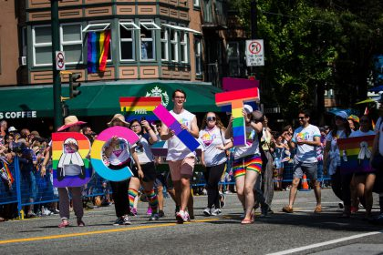 Photo from BCIT pride parade of a group of people holding up the letters BCIT with rainbow design